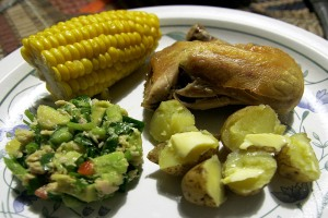 Tuna avocado salad with boiled baby potatoes, corn on the cob, and roast chicken